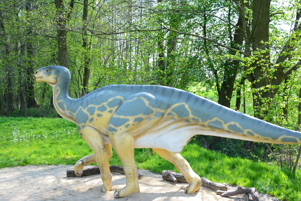 A replica of an Iguanodon, it's a dinosaur walking on four legs blue and yellow in color