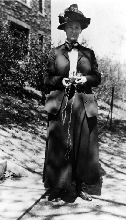 Florence Bascom wearing a jacket and a bow around her neck. She also has a large hat. She is holding a compass in her hands.