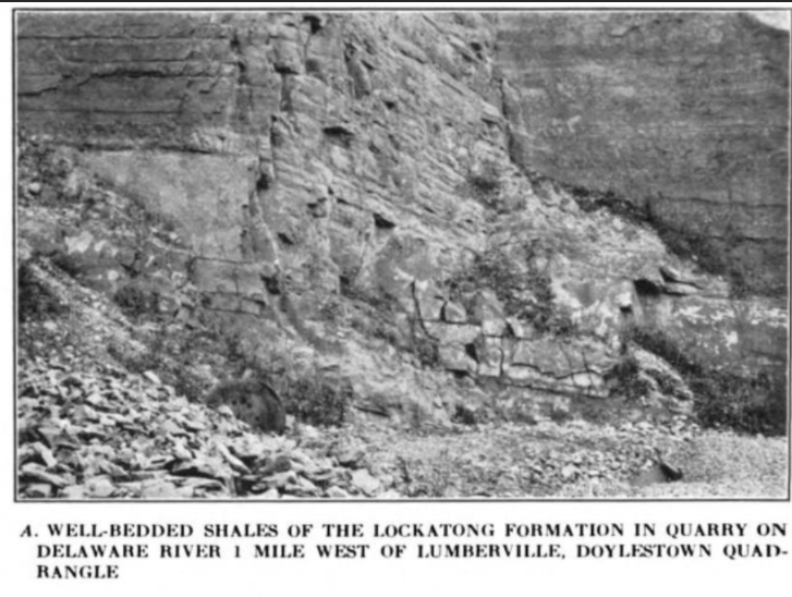 An old photograph of a rock face on a cliff. The rocks are blocky and fractured and there are rubble piles at the base of the cliff
