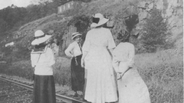 Four women standing on train tracks in front of a geologic otucrop.