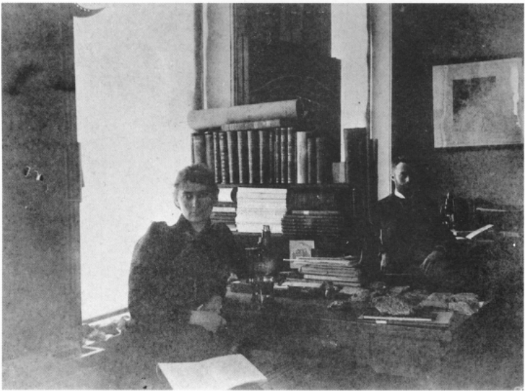 A young woman and a bearded man sit at a lab desk with books and microscopes