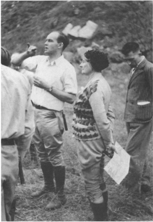 Florence Bascom with three other men in the field looking off to the distance. Bascom is holding a map and compass.
