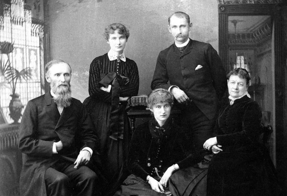 Photograph of a family of five in old style clothes. In the front are an older man and woman and a young woman. In the back stand a young woman and young man.