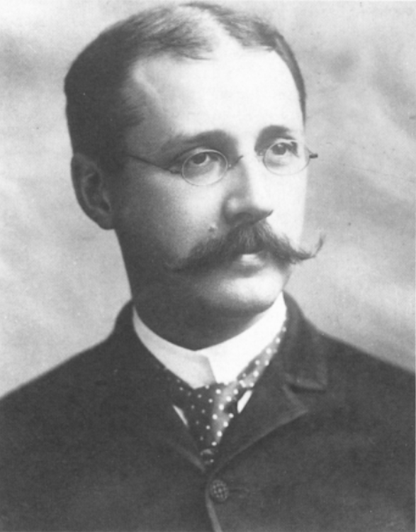 A photograph of a man wearing glasses and a long, curled mustache. Wearing old style formal clothes