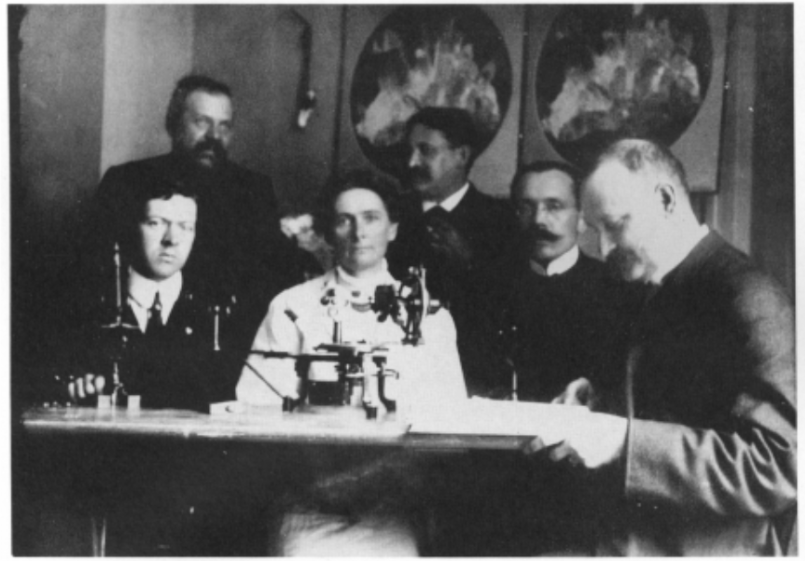 Photograph of five men and one woman wearing old style clothes sitting in front of a scientific instrument.
