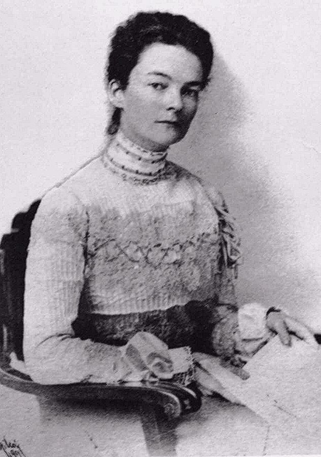 A portrait of a woman with short hair. She is wearing an older style dress