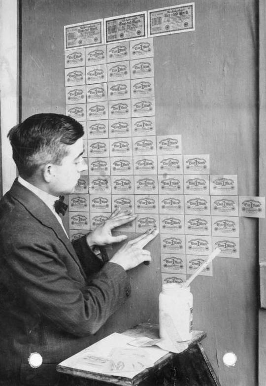 A man pasting old German banknotes on a wall as wallpaper