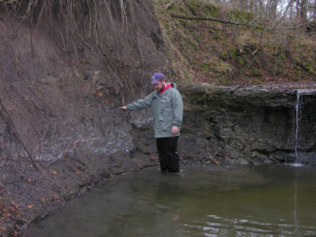 Image of me standing in cold water next to a rock outcrop illustrating fieldwork difficulties.