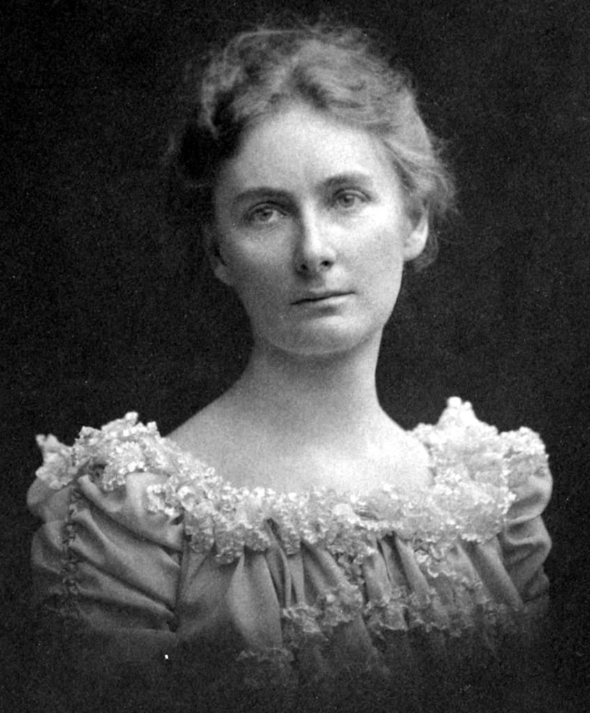 A portrait of a young woman with short wavy hair waring an older style, frilly dress