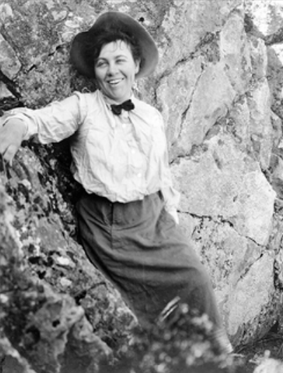 A smiling woman leaning up against a rockface wearing a hat, blouse, skirt, and small dark bowtie