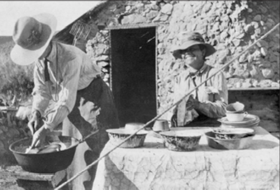 Two women with hats cleaning dishes at a campsite with a cabin behind them