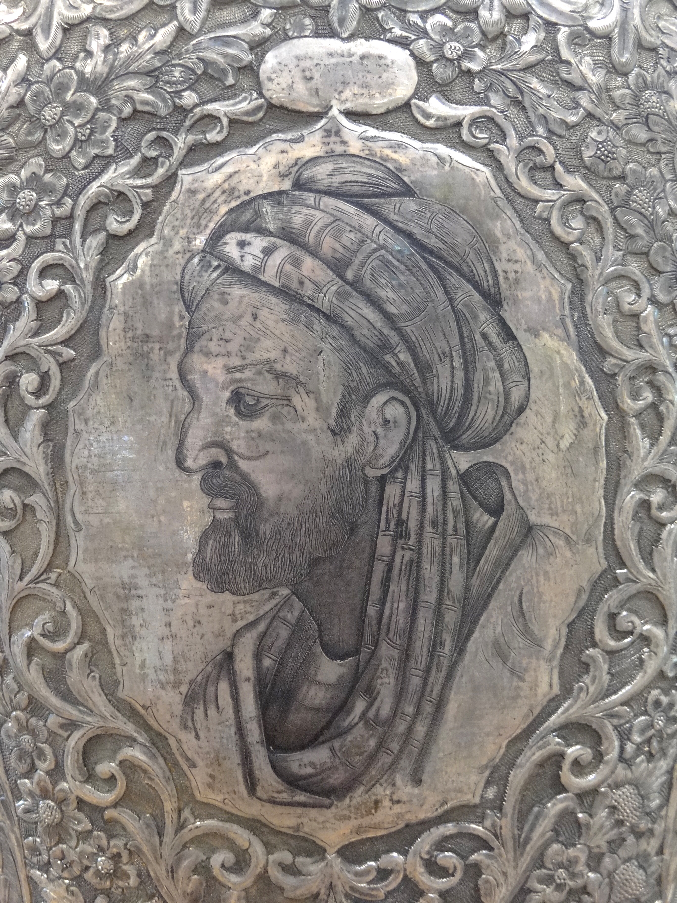 Profile portrait of Ibn Sina wearing a turban etched on a silver vase