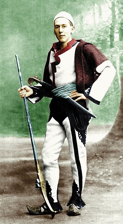 A young man dressed in traditional Albanian clothes holding a long rifle