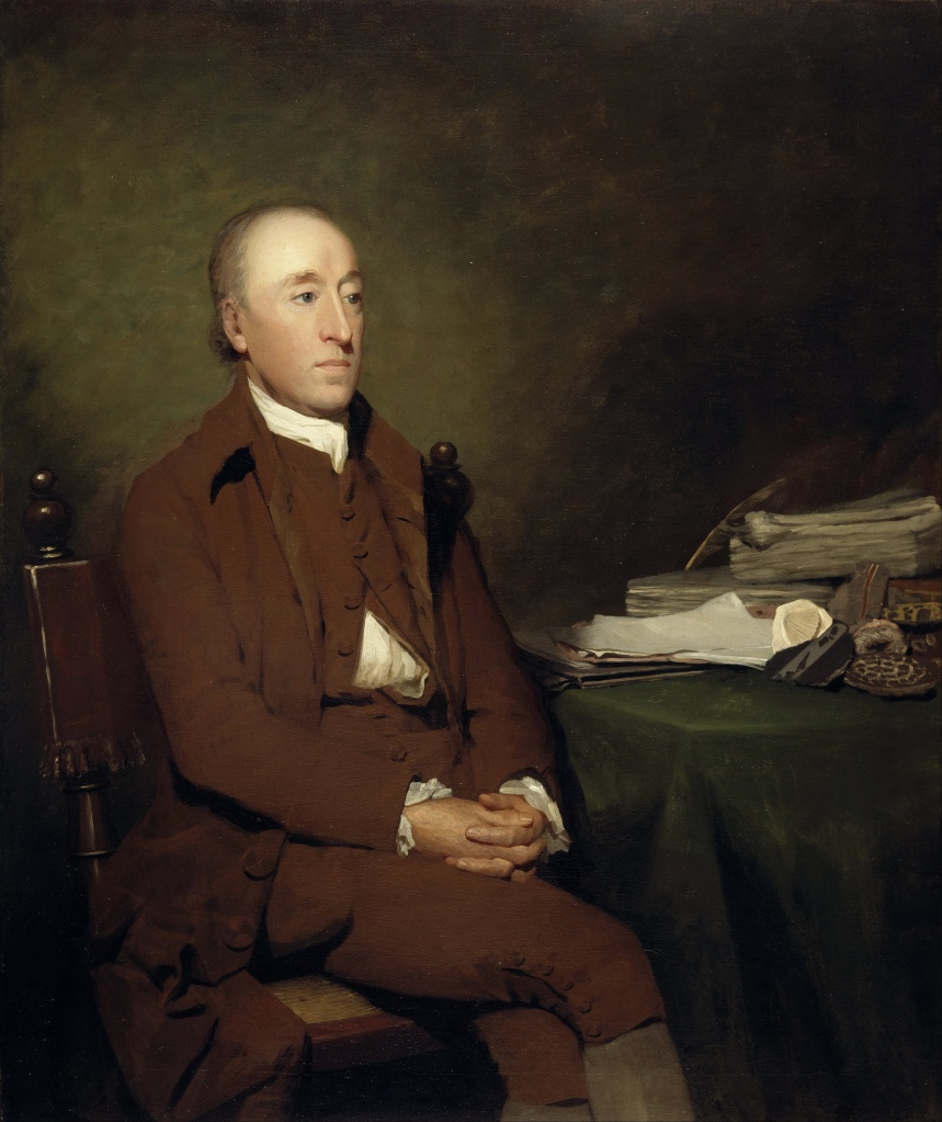 James Hutton sitting at a desk. He has short hair, and is wearing a brown coat and vest with hands folded on his lap.
